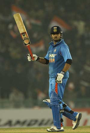 Suresh Raina waives his bat after completing half century against England